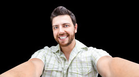 Happy young man taking a selfie photo isolated on black background Royalty Free Stock Photos