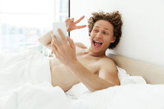 Happy young man taking selfie and showing peace gesture Royalty Free Stock Photography