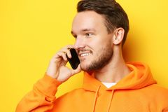 Happy young man talking on cell phone over yellow  background Stock Photography