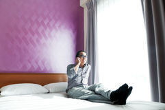 Happy young man talking on mobile phone in bedroom Royalty Free Stock Photo