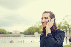 Happy young man talking on mobile phone Royalty Free Stock Image
