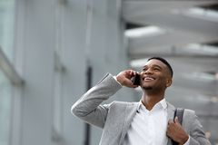 Happy young man talking on mobile phone inside building. Close up portrait of a happy young man talking on mobile phone inside building Stock Photography