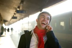 Happy young man talking on mobile phone at train station Royalty Free Stock Image