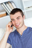 Happy young man talking on phone sitting on a sofa Royalty Free Stock Photo