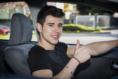 Happy young man or teenager doing thumb up driving Stock Photo