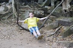 Happy young man, the teenager, the tourist, shakes on a liana as on a swing on Beng Mealea temple  ruin in the Koh Ker complex, Si. Em Reap, Cambodia Royalty Free Stock Images