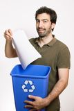 Happy young man throw paper in blue basket Stock Photography