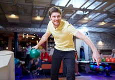 Happy young man throwing ball in bowling club. People, leisure, sport and entertainment concept - happy young man throwing ball in bowling club Royalty Free Stock Photos
