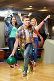 Happy young man throwing ball in bowling club Royalty Free Stock Images