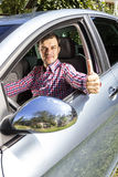 Happy young man with thumb up at the wheel Royalty Free Stock Photo