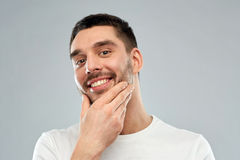 Happy young man touching his face or beard Stock Images