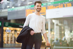 Happy young man traveling. Attractive smiley casual young man carrying a suitcase at a train station lobby; travel concept Royalty Free Stock Photography