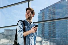 Happy young man traveling with bag and mobile phone Stock Photography