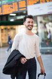 Happy young man traveling. Vertical shot of an attractive smiley casual young man, carrying a suitcase at a train station lobby Stock Photos