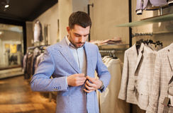 Happy young man trying jacket on in clothing store stock images