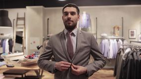 Happy young man trying suit at clothing store stock video footage