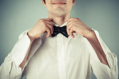 Happy young man tying abow tie Royalty Free Stock Photos