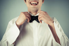 Happy young man tying abow tie royalty free stock photo