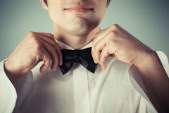 Happy young man tying a bow tie. Closeup on a happy young man tying a bow tie Stock Image