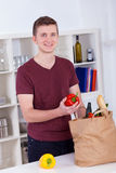 Happy young man unpacking groceries in the kitchen Stock Photo