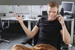 Happy young man using cell phone at office Stock Photo