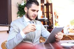 Happy young man using digital tablet in cafe Stock Photo
