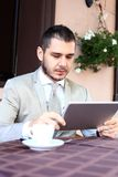 Happy young man using digital tablet in cafe Stock Image
