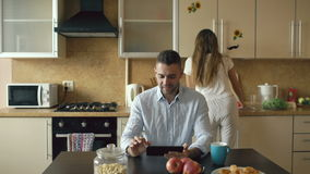Happy young man using digital tablet computer sitting in the kitchen while his girlfriend cooking at home stock video