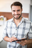 Happy young man using digital tablet in kitchen Royalty Free Stock Photos
