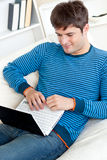 Happy young man using his laptop lying on the sofa Royalty Free Stock Photography