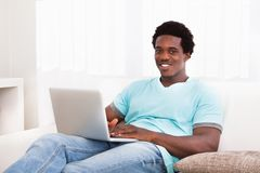 Happy young man using laptop Stock Photos