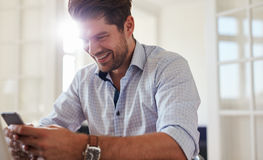Happy young man using mobile phone at home Royalty Free Stock Images