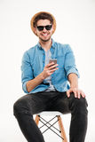 Happy young man using mobile phone and smiling Royalty Free Stock Photography