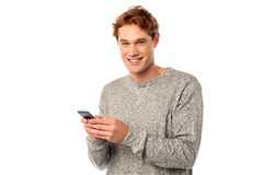 Happy young man using mobile. Young man reading emails from a smartphone Royalty Free Stock Photo