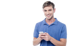 Happy young man using mobile. Young man reading emails from a smartphone Stock Photo