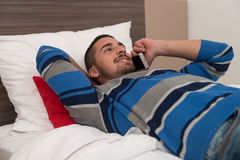 Happy Young Man Using Phone On Bed Stock Images