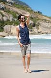 Happy young man on vacation walking barefoot on beach Royalty Free Stock Photos