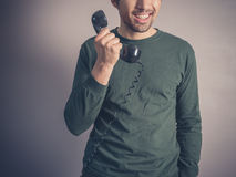 Happy young man with vintage phone Stock Photography