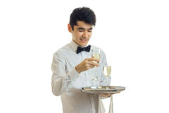 Happy young man waiter in uniform with two glasses of wine on silver tray smiling. Isolated on white background stock photos