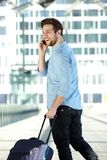 Happy young man walking at airport with bag and mobile phone. Portrait from behind of a happy young man walking at airport with bag and mobile phone Stock Image