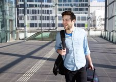 Happy young man walking with bags at station Royalty Free Stock Image
