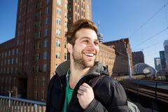 Happy young man walking in the city with bag. Close up portrait of a happy young man walking in the city with bag Royalty Free Stock Image