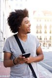 Happy young man walking in the city with cellphone Royalty Free Stock Photos