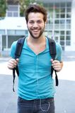 Happy young man walking outdoors with bag. Close up portrait of a happy young man walking outdoors with bag Royalty Free Stock Photo