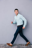 Happy young man walking over gray background Royalty Free Stock Photos