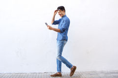 Happy young man walking on street looking at mobile phone