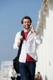 Happy young man walking and talking on cell phone Stock Image