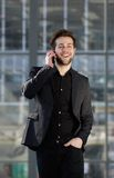 Happy young man walking and talking on mobile phone Stock Photography