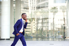 Happy young man walking and talking on mobile phone Stock Image