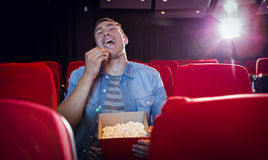 Happy young man watching a film Stock Photography